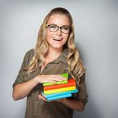 Portrait of cheerful smiling clever student girl with books over gray background, education in the university, enjoying start of educational process poster
