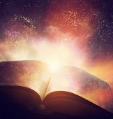 Open old book merged with magic galaxy sky, universe, stars. Concept of literature, fantasy, horoscope, religion etc. poster