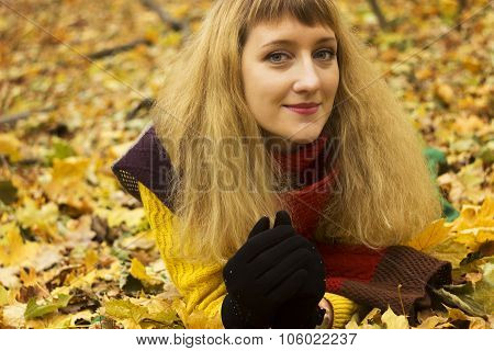 Young beautiful girl lying on autumn leaves