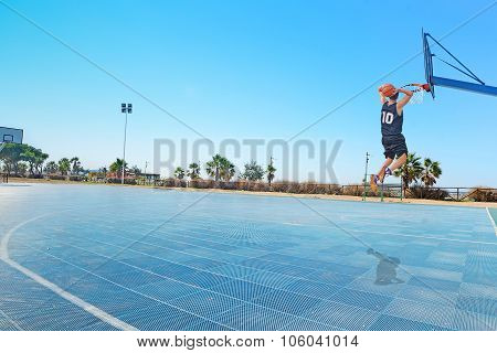 Two-handed Slam Dunk In A Blue Playground