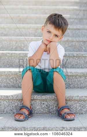 The boy sitting on the stairs in the underpass