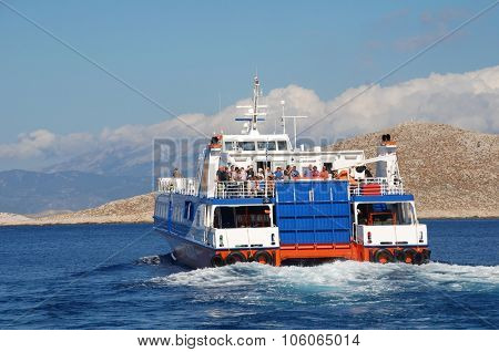 HALKI, GREECE - JUNE 9, 2015: Catamaran ferry Dodekanisos Express heads past Nissos island while departing Emborio harbour on the Greek island of Halki. The 40mtr vessel was built in Norway in 2000.