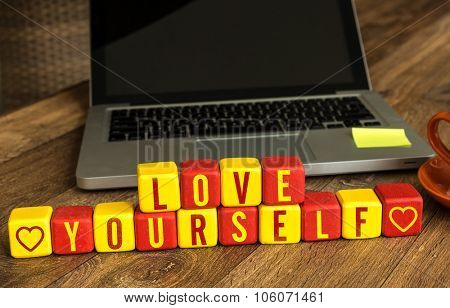 Love Yourself written on a wooden cube in front of a laptop poster