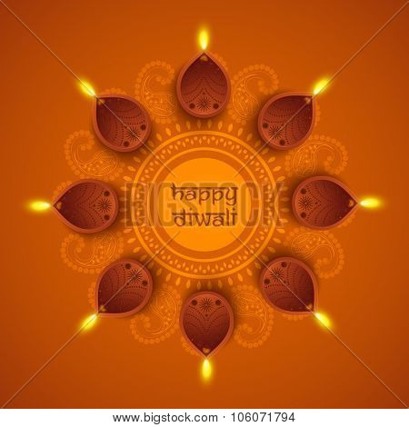 Traditional illuminated oil lit lamps on beautiful floral rangoli for Indian Festival of Lights, Happy Diwali celebration.