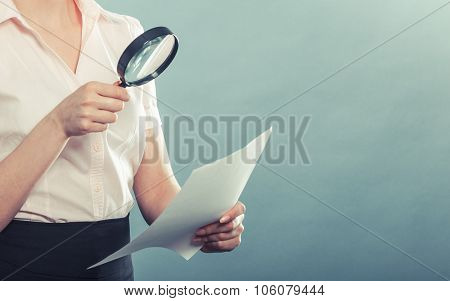 Woman Uses Magnifying Glass To Check Contract