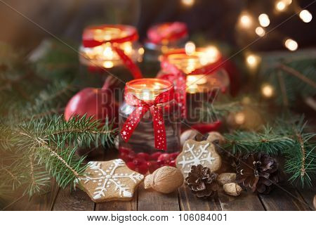 Christmas decorations. Candles in glass jars with fir  and gingerbread cookies