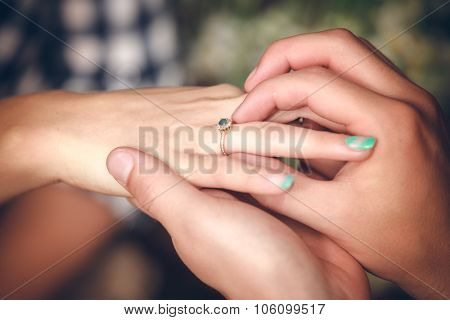 Man placing engagement ring on the finger of his fiance