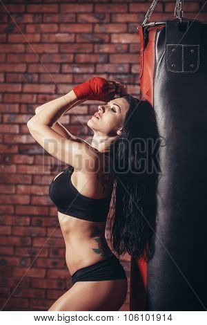Young beautiful sexy boxer woman with red boxing bandage on hands. punching bag, on the background wall of red brick. poster