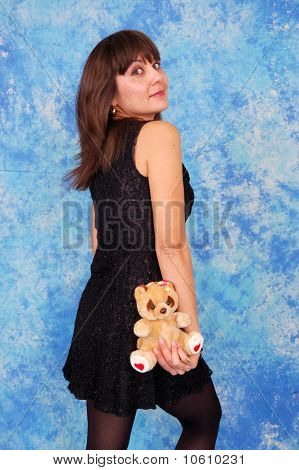Girl in black with a teddy bear in a hand