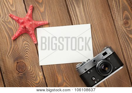 Travel and vacation photo frame, starfish and camera on wooden table