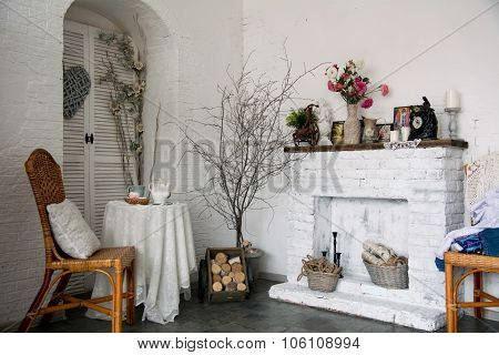 The Design Interior Rustic Room With A Fireplace, Flowers, Chairs And A Table With Cups Of Tea