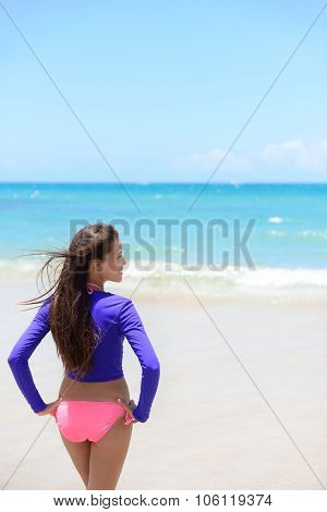 Woman relaxing on beach looking at the waves in sun protective swimwear t-shirt / rashguard to protect skin against rashes and uv rays during swimming or surfing. poster