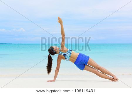 Fitness woman strength training her body core muscles with yoga pose. Athlete planking on one arm doing side plank and hip lift.