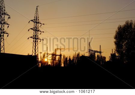 high-voltage line towers in front of a fuming factory chimney during sunset. shot in poltavska region poster