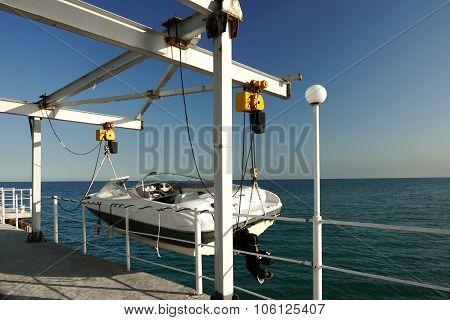White Motor Boat Hanging On The Pier Davit