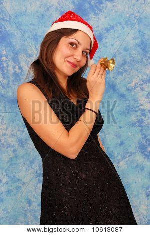 Image of a girl in a christmas hat holding a bell