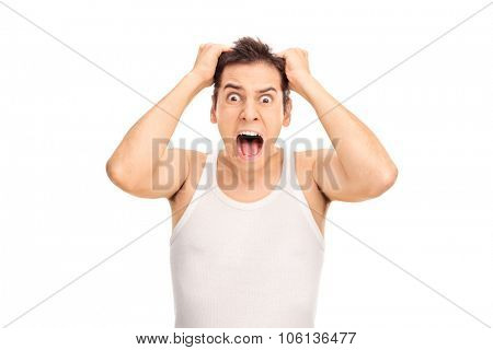 Studio shot of a furious young man yelling and pulling his hair isolated on white background