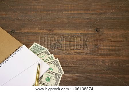 Brown Wood Table With Notebook, Money  And Gold Ink Pen