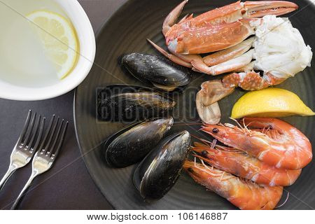 Top down view of seafood on plate and finger bowl
