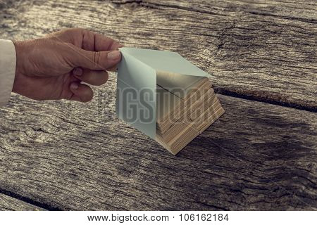 Retro Image Od Male Hand Covering A House Miniature Made Of Wooden Pegs With A Paper Roof