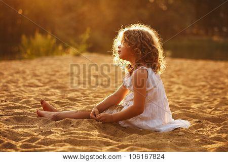 Little Girl In Dress Sitting On The Sand
