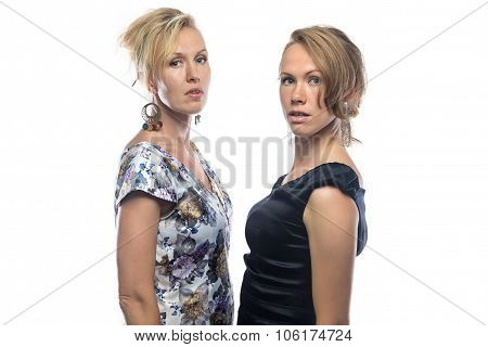 Two serious sisters on white background