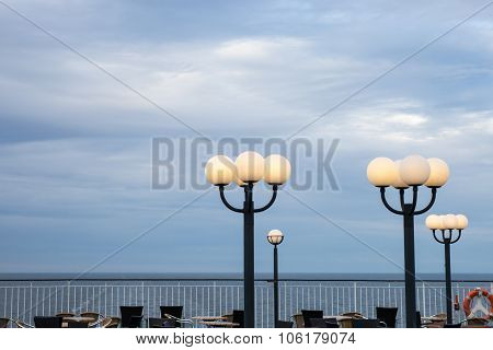 Burning Lamps Against The Storm Sky