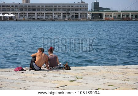 Trieste, Italy - August 18, 2015: Young Couple Seats On Molo Audace