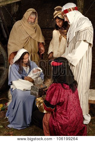 Live Christmas nativity scene reenacted in a medieval barn - the baby is a doll