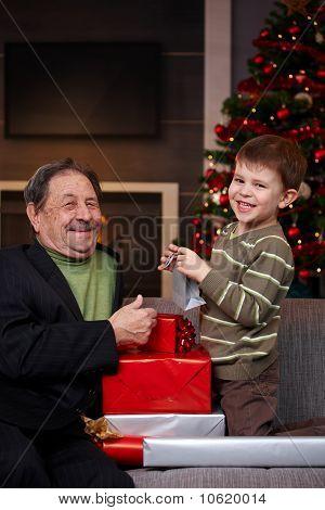 Boy Giving Christmas Present To Grandfather