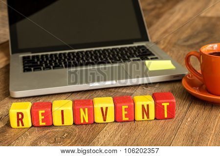 Reinvent written on a wooden cube in front of a laptop