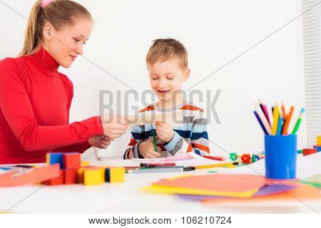 Woman helping prescholler kid to cut the paper