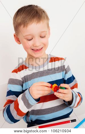 Boy making toy from mosaic