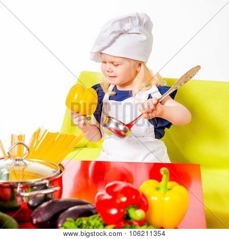 Cute blonde girl in costume of cook holding yellow pepper