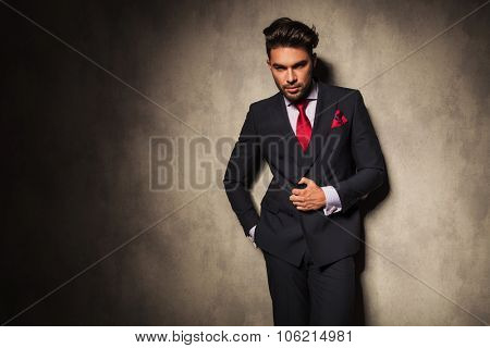 Attractive young business man closing his jacket while leaning on a grey wall.