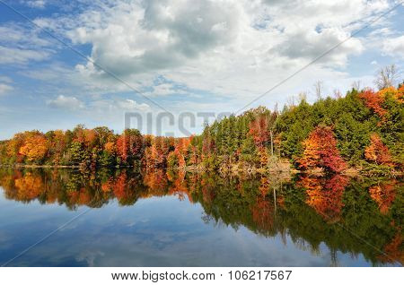 Beautiful autumn lake reflecting red fall colors in its clear water