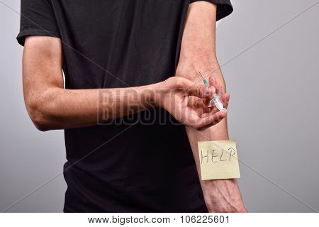 Hand with heroin syringe with post it that says help poster