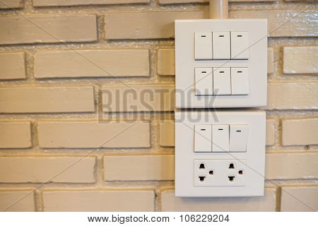 Dimmer Switch And Light Switch On Switchboard.over  Brick Wall