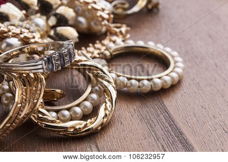 several fashionable women's jewelry on wooden surface