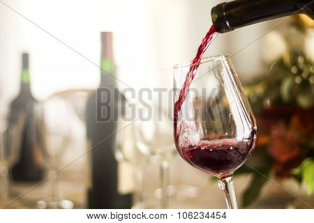red wine pouring on glass on wood background