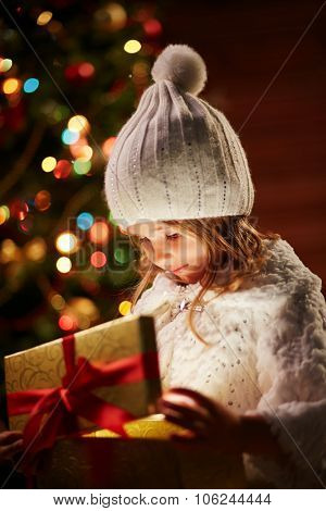 Little girl in white winterwear looking at present in golden giftbox with red ribbon