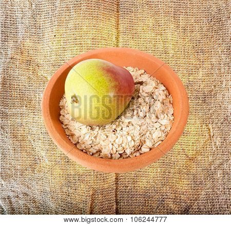 Oatmeal and pear in ceramic plate on sackcloth background