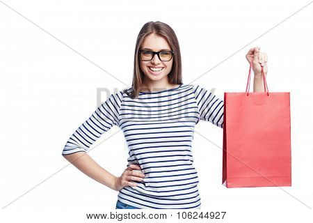 Pretty young shopper with red paperbag looking at camera