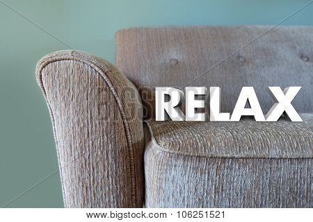 Relax word in white 3d letters on a couch to illustrate desire to take a break and rest on plush furniture