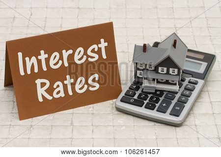 Mortgage Interest Rates, A Gray House, Brown Card And Calculator On Stone Background