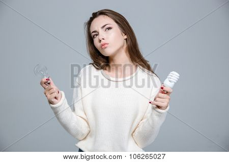 Portrait of a thoughtful woman holding saving light bulb and normal light bulb over gray background