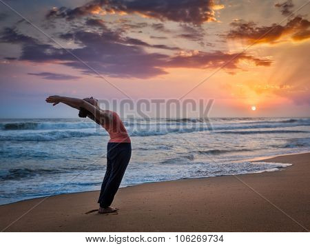 Young sporty fit man doing yoga Sun salutation Surya Namaskar pose Hasta Uttanasana on tropical beach on sunset