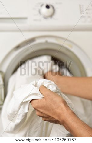 closeup of a young man introducing or taking out a white sheet into a washing machine or a clothes dryer