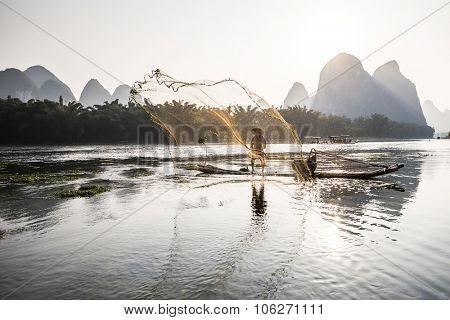 traditional cormorant fisherman throwing a net on Li river near Xingping, Guangxi province, China.