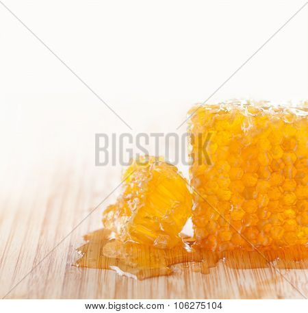 Sweet food concept. tasty honeycomb on the wooden table. White background.